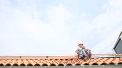 Man on roof top checking on solar panel installation Stock Footage