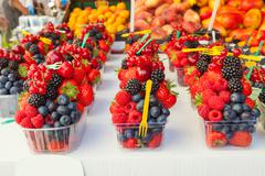 Colorful arrangement of fresh fruit berries ready to eat on a market stall. - stock photo