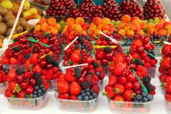 Colorful arrangement of fresh fruit berries ready to eat on a market stall. Stock Photos