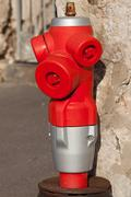 Red fire hydrant near a house wall - stock photo