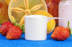 Plastic cup of protein powder with strawberries around Stock Photos