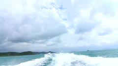 Speed Boat Back Trail Sea Ocean Waves Tropical Island Sky Clouds Fast Hand Held - stock footage