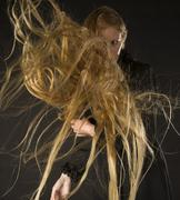 Blond Woman with Wind Blowing Through Long Hair - stock photo