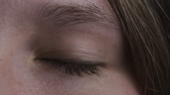 Closeup dark footage of open and blinking green teen girl eye in 180fps slow Stock Footage