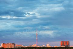 blue rainy clouds over illuminated by sunset city - stock photo