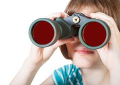front view of girl looks through field glasses - stock photo