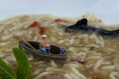 Miniature man fishing in soup Stock Photos
