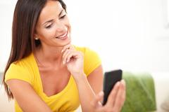 Calm woman with straight hair using a cell phone with one hand on her chin Stock Photos