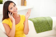 Relaxed woman listening to her mobile phone while holding one hand raised - c - stock photo
