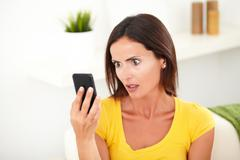 Head and shoulders portrait of a shocked woman looking to her cell phone - fo Stock Photos