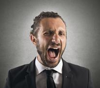 Furious businessman screaming - stock photo