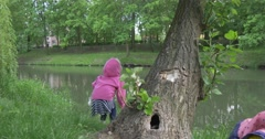 Back Close-up View Child Girl on the Lakeside Jumping up Stock Footage