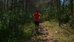 Slow motion - Back view of a man running in forest - stock footage