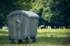 Green dumpster in forest for tourists - stock photo