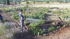Laughing Girl Sprays Camera at Community Garden Stock Footage