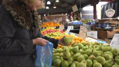 Lady selecting pears at produce market Stock Footage