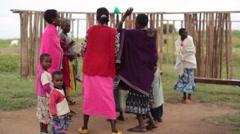 Samburu women and children sing, dance and drum, Kenya, Africa, long shot Stock Footage