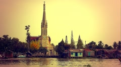 Mekong Delta - May 2015: Boats on river with cathedral in Cai Be. Retro look Stock Footage