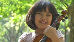 Little Asian girl holding violin in the park Stock Footage