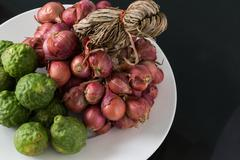 Bergamot and shallot in a plate on black background Stock Photos