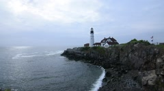 Lighthouse and rocky point in Portland, Maine under cloudy sky Stock Footage
