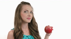 Thoughtful young woman eating a dark red apple on a white background. 4K raw Stock Footage