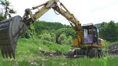 backhoe with a big bucket dig a lake in the woods in slow motion - stock footage