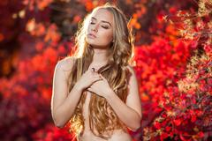 young woman on a background of red and yellow autumn leaves with beautiful curly - stock photo