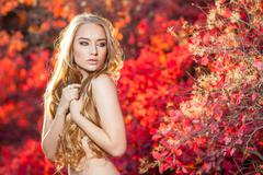 Young woman on a background of red and yellow autumn leaves with beautiful curly Stock Photos