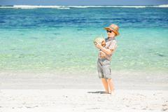 Happy young boy staying on beautiful ocean beach wearing hat and sunglasses Stock Photos