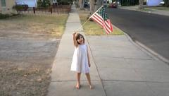 Cute 5 year old girl in white dress waving US flag. Slow motion. Stock Footage