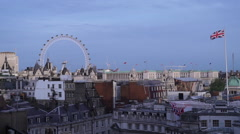 London Eye and a British flag from a rooftop nearby - stock footage