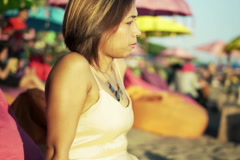 Young beautiful pensive woman sitting alone on the cafe by the beach  NTSC Stock Footage