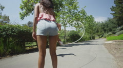 Young girlfriends jumping rope at the park - stock footage