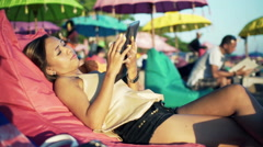 Young attractive woman with tablet computer lying on the cafe by the beach  HD Stock Footage