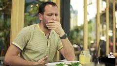 Young man gets stomach ache during breakfast in cafe  HD Stock Footage