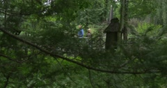Two people pass by Birdhouse, Animal House in The Park Stock Footage
