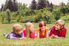 Upbeat children lying on grass in raw - stock photo