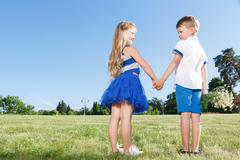 Upbeat little kids holding theur hands together - stock photo