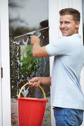 Portrait Of Man Cleaning House Windows - stock photo
