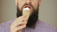 Cute Beard man in plaid shirt with a bow tie eating ice cream Stock Footage