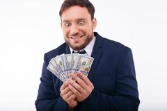 Cheerful young guy is crazy about dollars - stock photo
