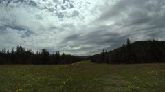 Rotational hyperlapse on quick flick of clouds and sunshine in the meadow - stock footage