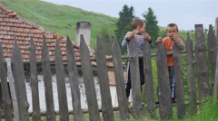 Two children on a wooden fence in a mountain hamlet Stock Footage