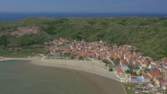 Aerial - View at the lower and upper island village next to the sandy bay Stock Footage