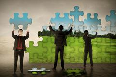 Business teamwork assembling puzzle pieces create green environt Stock Photos