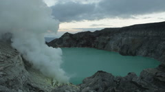 Kawah Ijen volcanic crater lake and toxic sulfur fume,workers extract sulfur Stock Footage