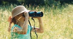 Portrait laughing young naturalist through binoculars watching wildlife - stock footage