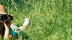 Young naturalist explorer with binoculars watching wildlife. Child lying - stock footage