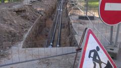 New heating system pipes in trench and road signs Stock Footage